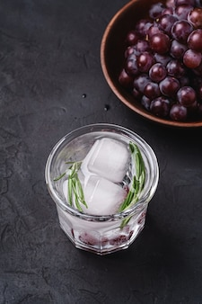 Świeża lodowata woda gazowana w szkle z liściem rozmarynu w pobliżu drewnianej miski z jagodami winogron, powierzchnia z ciemnego kamienia, kąt widzenia