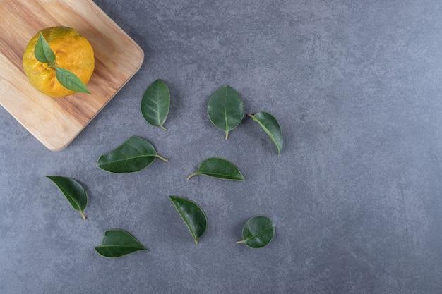Świeża mandarynka na drewnianej desce i liściach.