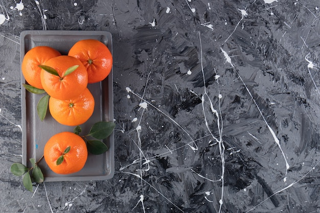 Świeża mandarynka na drewnianym talerzu, na stole mieszanym.