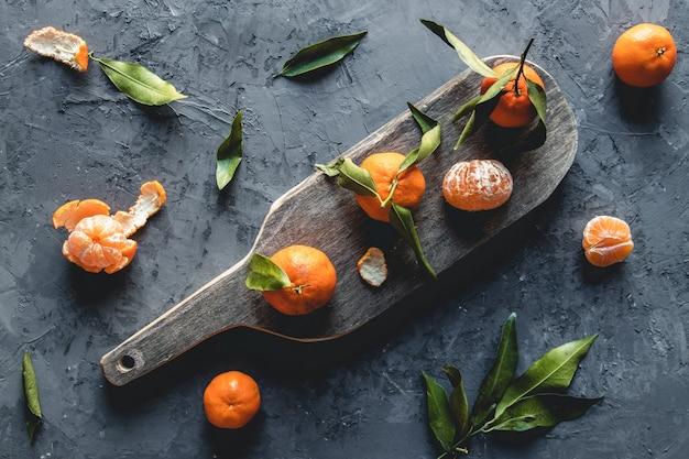 Świeża mandarynka pomarańczowa na drewnianej desce do krojenia. eko wegetarianin. pnov2019