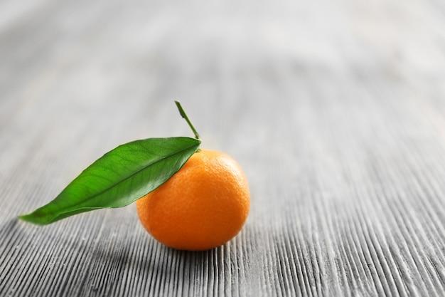 Świeża mandarynka z liściem na drewnianym stole, zbliżenie