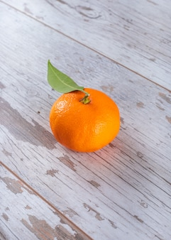 Świeża mandarynka z liśćmi na drewnianym stole