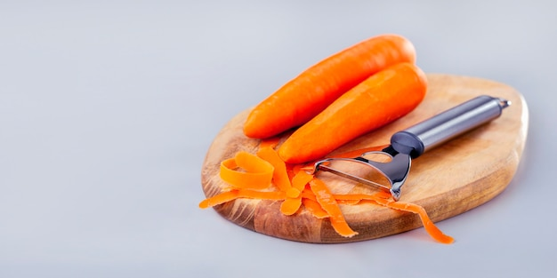 Świeża marchewka z obieraczką na drewnianej desce na szarym tle, projekt transparentu. warzywa dla zdrowej diety.