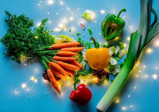 Świeża marchewka z porem, sałatą, papryką i bajkowymi światłami na niebieskiej powierzchni