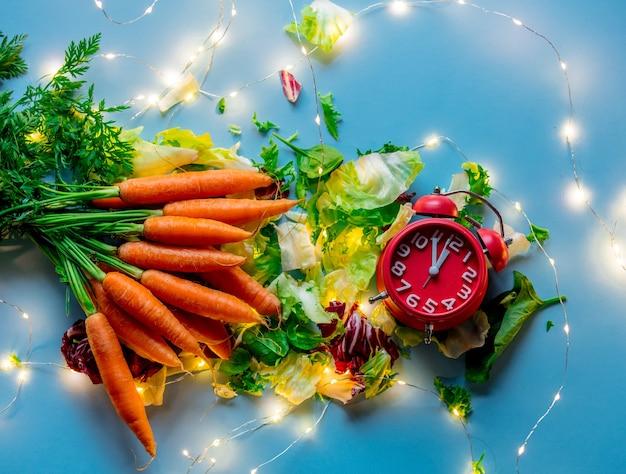 Świeża marchewka z sałatką, budzikiem i bajkowymi światłami na niebieskiej powierzchni