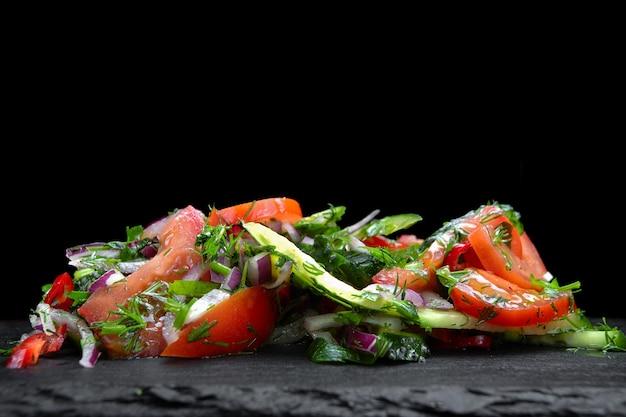 Świeża mieszanka sałat z cykorią i pomidorkami cherry na czarnym kamiennym łupku