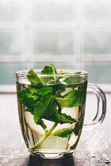 Świeża miętowa herbata w pobliżu okna. przytulny dom lub zdrowie