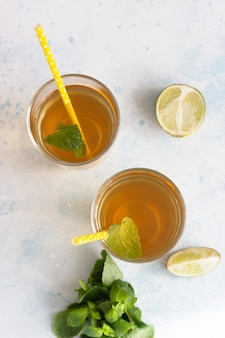 Świeża naturalna zielona miętowa herbata ziołowa w szklankach ze świeżymi liśćmi mięty i limonką