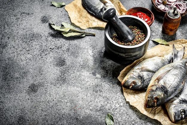 Świeża nieprzygotowana ryba dorado z sosem i przyprawami.