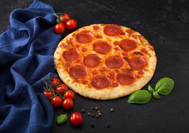Świeża okrągła pieczona włoska pizza pepperoni z pomidorami z bazylią na tle czarnego stołu w kuchni.