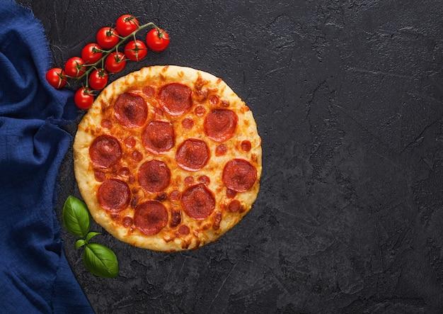 Świeża, okrągła pieczona włoska pizza pepperoni z pomidorami z bazylią