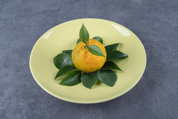 Świeża organiczna mandarynka z liśćmi na żółtym talerzu.