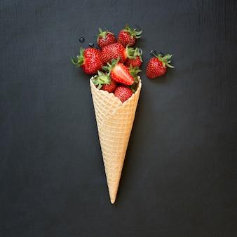 Świeża organicznie truskawka w lody rożku na czerni.
