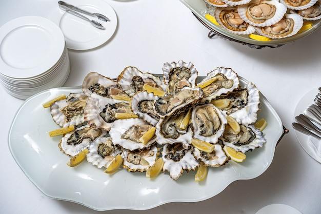 Świeża otwarta ostryga na białym talerzu. w restauracji