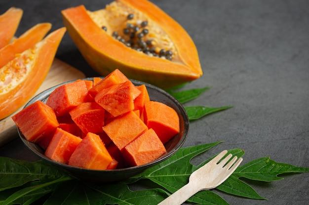 Świeża papaja, pokrojona na kawałki, ułożona na czarnym talerzu.