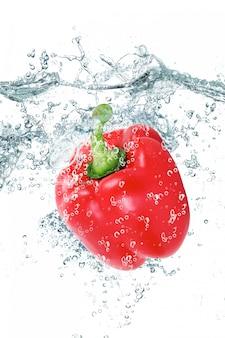 Świeża papryka spada w wodzie
