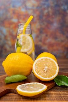 Świeża picie lemoniady z ziołami w szklance, limonce lub koktajlu mojito z cytryną na drewnianym stole na miejsce do kopiowania i rustykalnym metalowym tle grunge w gorące lato