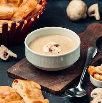 Świeża pieczarkowa zupa na drewnianej desce