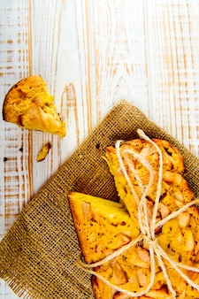 Świeża piekarnia. odgórny widok piec kulebiak z jabłkami na parciaku na biały drewnianym. styl rustykalny.