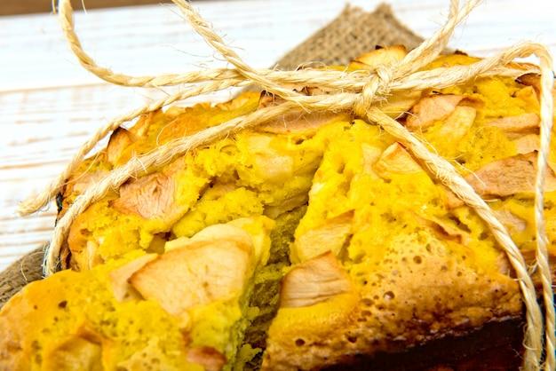 Świeża piekarnia. zakończenie piec kulebiak z jabłkami na parciaku na biały drewnianym. styl rustykalny.