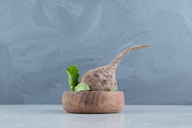 Świeża pietruszka i rzodkiewki w misce, na marmurowym tle.