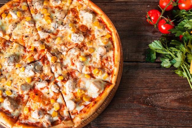 Świeża pizza hawajska serwowana na rustykalnym drewnianym stole ze składnikami, widok z góry. zdjęcie menu.
