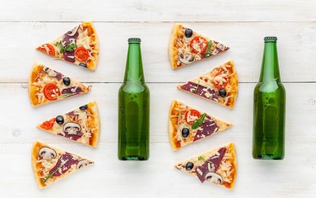 Świeża pizza w rustykalnym włoskim stylu z suszonymi oliwkami, pieczarkami i trzema rodzajami sera na jasnym drewnianym tle z butelką zimnego piwa
