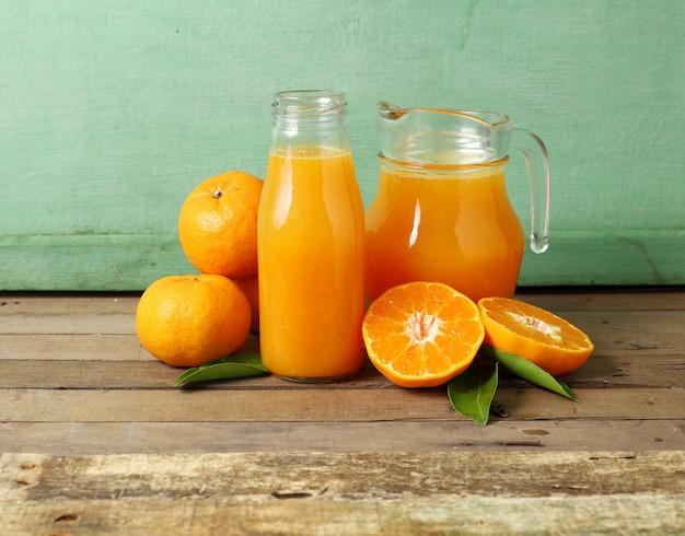 Świeża plasterek pomarańcze i butelka sok na drewnianym tle
