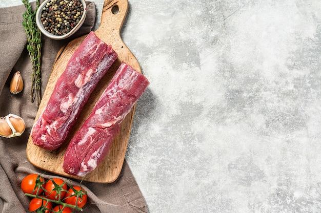 Świeża polędwiczka wieprzowa. surowe mięso filetowe. szare tło