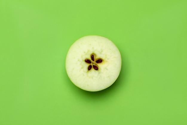 Świeża połowa jabłka z nasionami na zielonym tle, widok z góry.