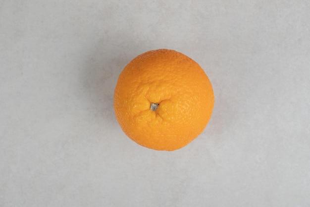 Świeża pomarańcza na szarej powierzchni.