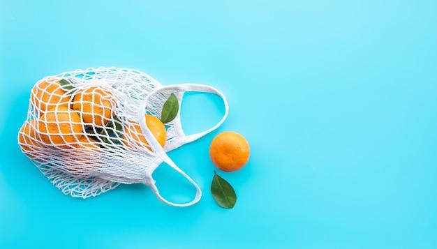 Świeża pomarańcza z ogrodu w szydełkowej torbie zdrowej i naturalnej koncepcji