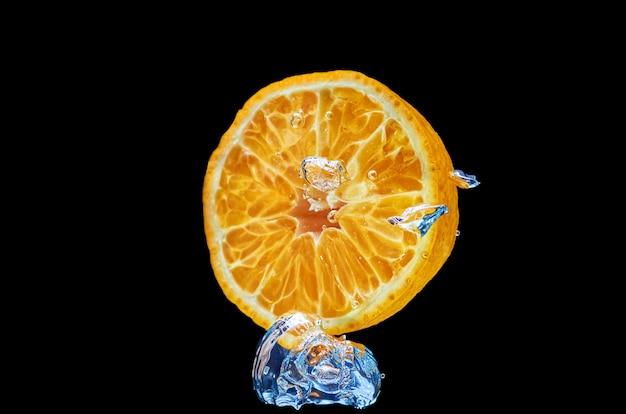Świeża pomarańcze spada w wodzie z pluśnięciem na czarnym tle