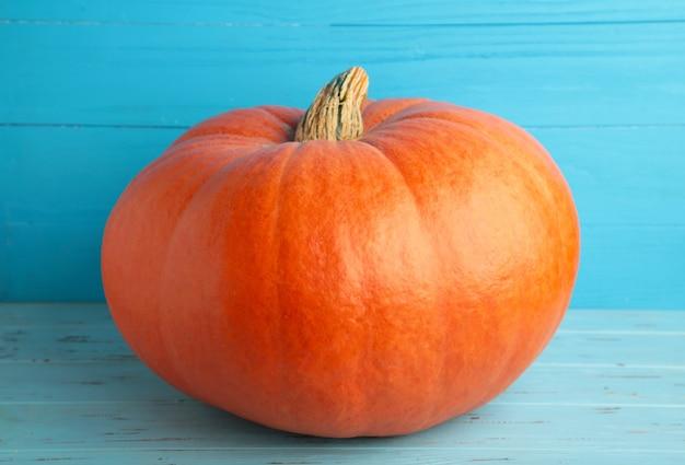 Świeża pomarańczowa dynia na niebieskim tle. jesienna kompozycja