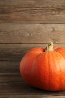 Świeża pomarańczowa dynia na szarym tle. jesienna kompozycja. zdjęcie pionowe