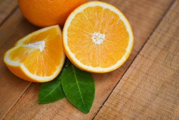 Świeża pomarańczowa plasterek połówka i pomarańczowego liścia owoc żniwa zdrowe pojęcie - pomarańczowa owoc na drewnianym