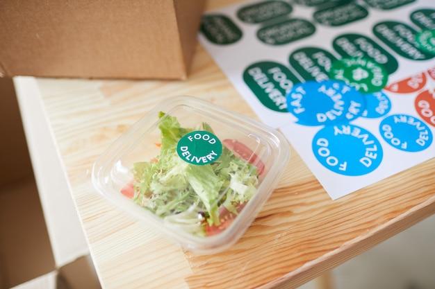Świeża porcja sałatki w plastikowym opakowaniu na drewnianym stole w usłudze dostawy zdrowej żywności