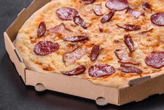Świeża pyszna pizza pieczona w piecu paleniskowym z czterema rodzajami mięsa i kiełbasą. kuchnia śródziemnomorska