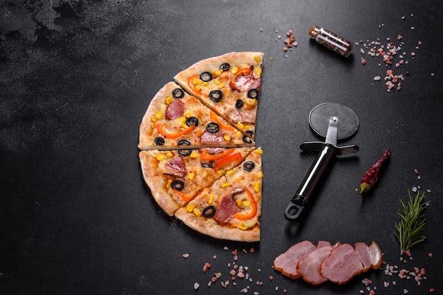 Świeża pyszna pizza pieczona w piecu paleniskowym z oliwkami, papryczką chili i szynką. kuchnia śródziemnomorska
