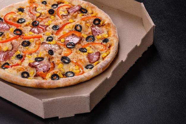 Świeża pyszna pizza pieczona w piecu paleniskowym z oliwkami, papryczką chili i szynką