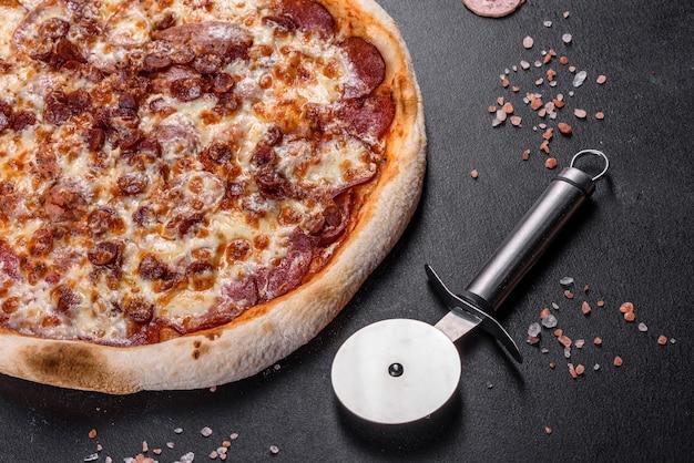 Świeża pyszna włoska pizza z czterema rodzajami mięsa na ciemnym betonowym tle. kuchnia włoska