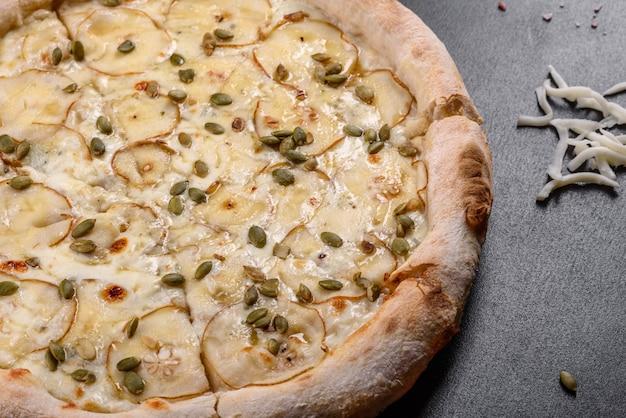 Świeża pyszna włoska pizza z gruszką i pestkami dyni na ciemnym tle betonu. kuchnia włoska
