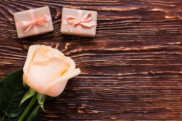 Świeża róża i kilka pakowanych prezentów na drewnie, widok z góry