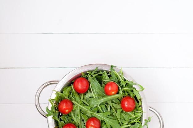 Świeża rukola sałatka z czereśniowymi pomidorami w pucharze na białym drewnianym tle. widok z góry