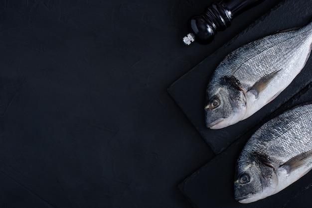 Świeża ryba dorada. dorado przy stole z czarnego łupka. widok z góry z miejscem na kopię.