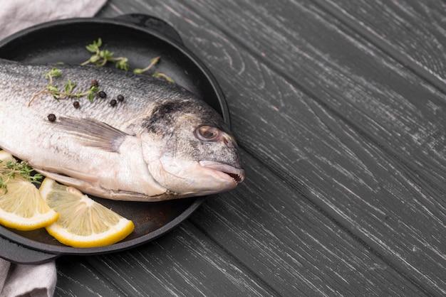 Świeża ryba dorada na talerzu z cytryną