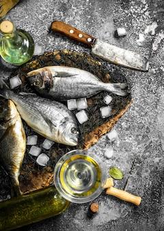 Świeża ryba dorado z kostkami lodu i kieliszkiem do wina.