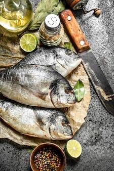 Świeża ryba dorado ze starym nożem i przyprawami.