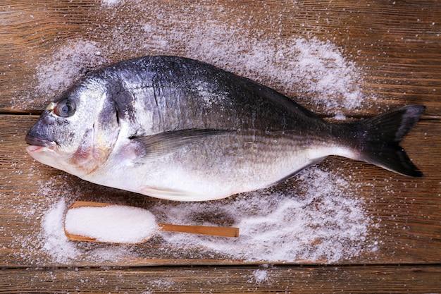 Świeża ryba i sól w łyżce na drewnianym stole