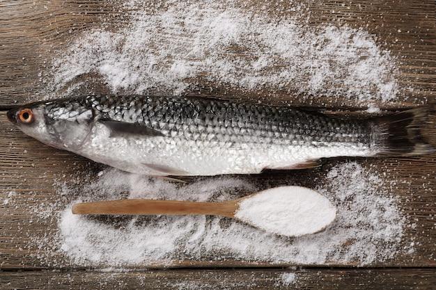 Świeża ryba i sól w łyżce na drewnianym